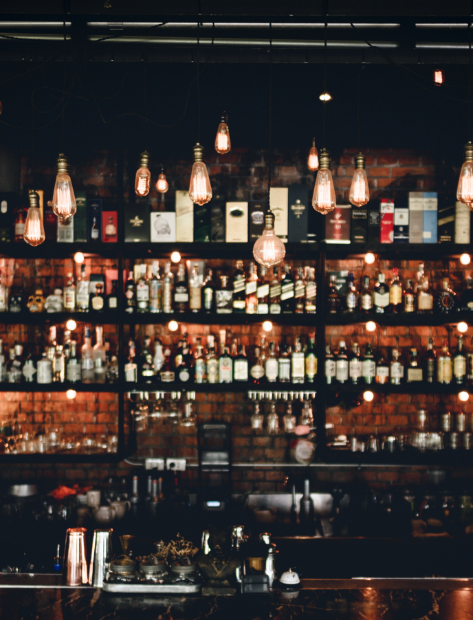 Bottles of drink against a wall in a bar